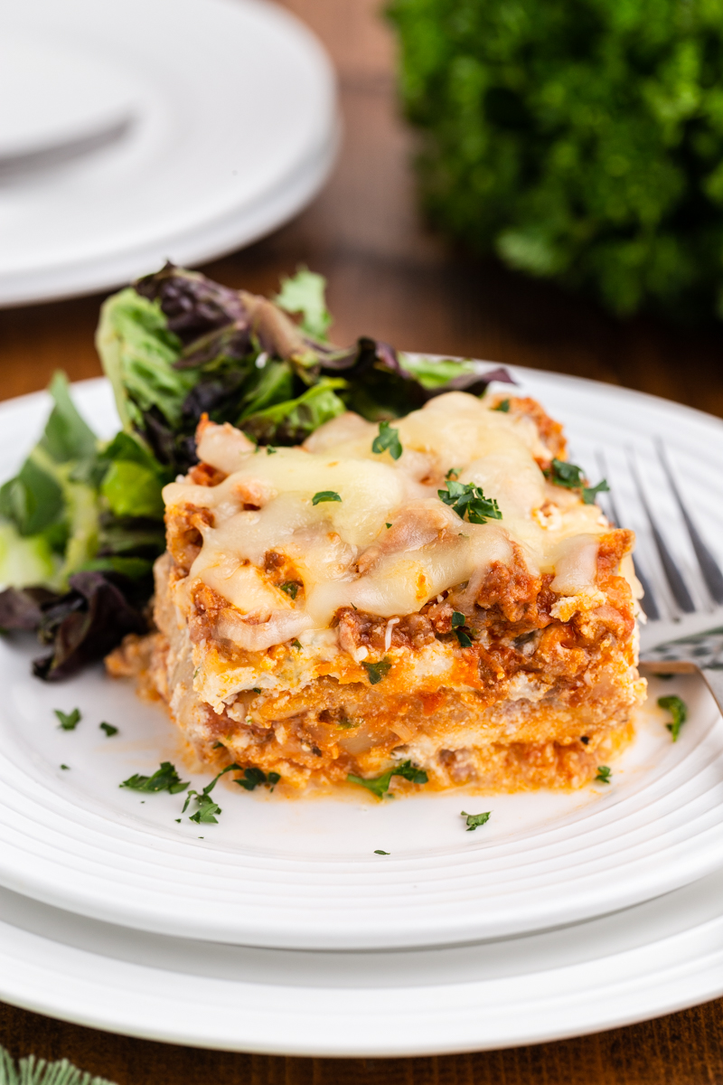 Another close up photo of a serving of keto lasagna on a white plate with a side salad.