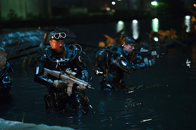 Military men and Toby Stephens stands in the water with guns drawn in the movie Hunter Killer