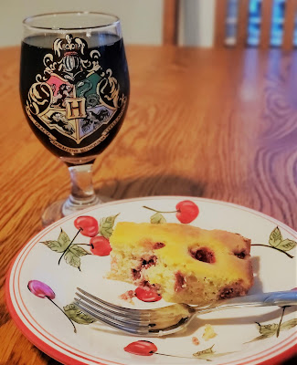 small piece of yellow cake with raspberries baked in, placed on a ceramic plate with cherries painted on it. Next to it is a wine goblet with the Hogwarts Houses painted on it.