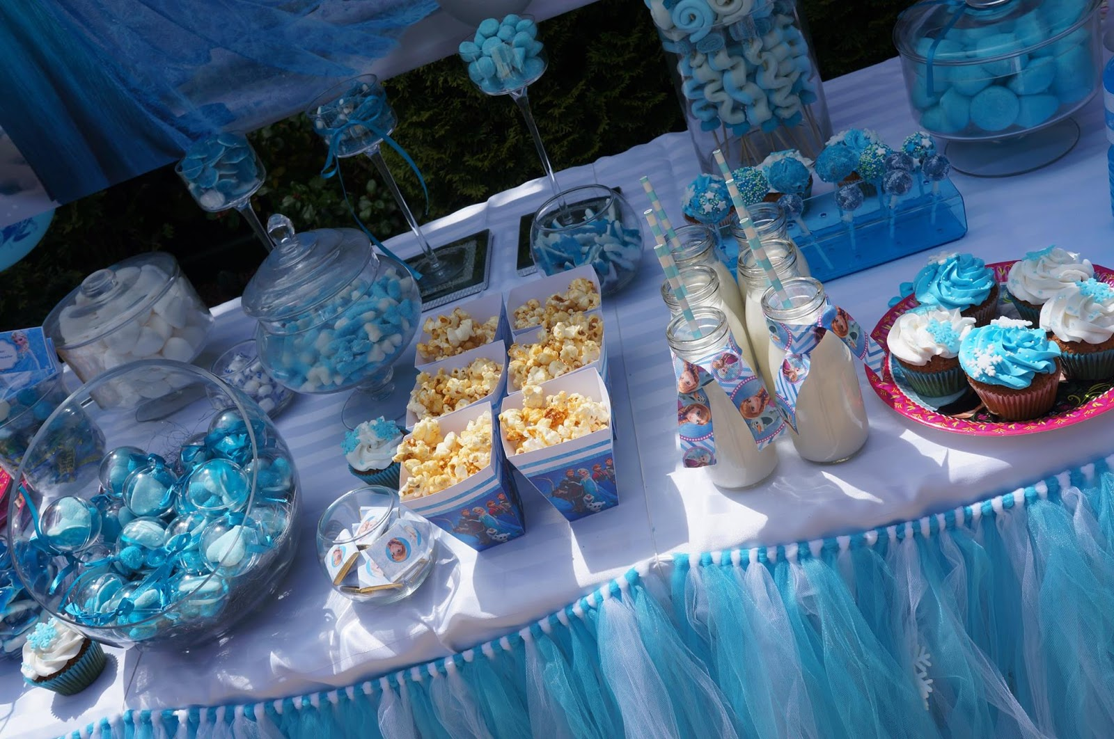 buffet de gourmandises sur table decoree en bleu sur le theme de la reine des neiges