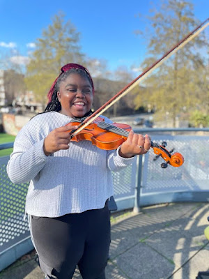 "Kadina, one of the pupils at CCHS, proudly standing with her new violin. She is 16 and said: ""I am really excited to learn the violin. I hope I don't break it!"""