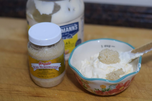 Mayonnaise and horseradish in a small mixing bowl with the containers beside it.