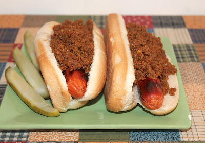 Finished hot dogs on a plate topped with hot dog sauce.