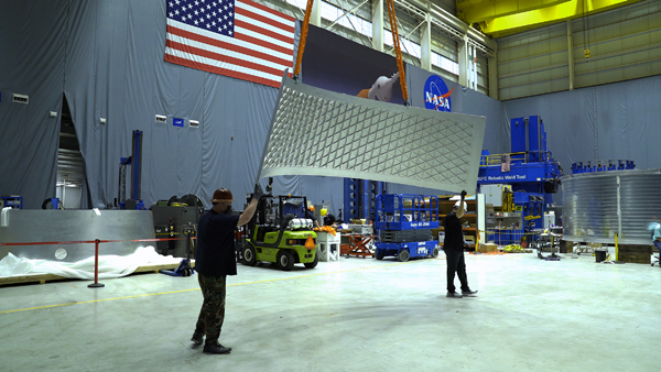 Two technicians move a panel for the Orion stage adapter--which will fly on the Artemis 2 mission to the Moon--across the floor at NASA's Marshall Space Flight Center in Huntsville, Alabama.
