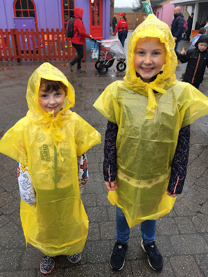 two children in yellow ponchos in the rain