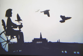 shadow puppetry, figure in wheelchair and skyline of Haarlem, Netherlands