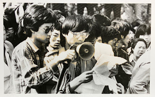 Black and white photograph of protestors reading a document over a megaphone