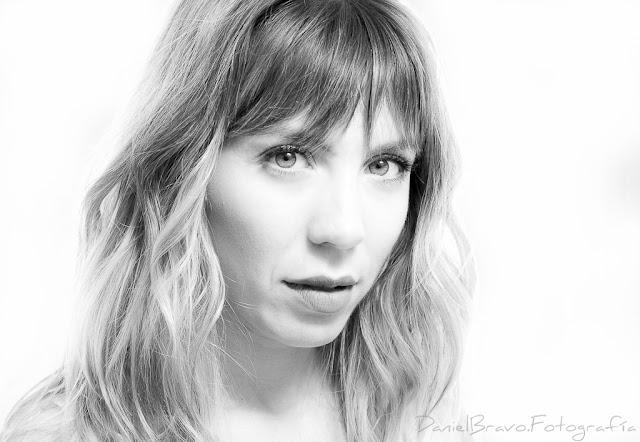 Imagen de una chica joven mirando a cámara con esquema de luces clamshell y fondo blanco. Fotografía en blanco y negro