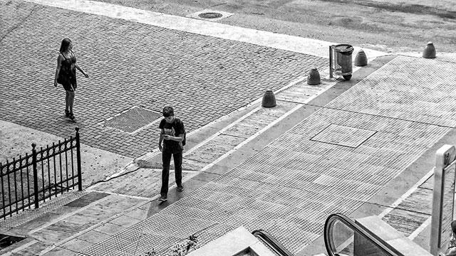 Dos personas ,una cruzando la calle la otra caminando en la vereda