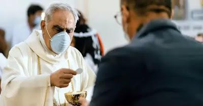 Un preot catolic care oferă unui enoriaș împărtășania - foto de Gabriella Clare Marino - unsplash.com