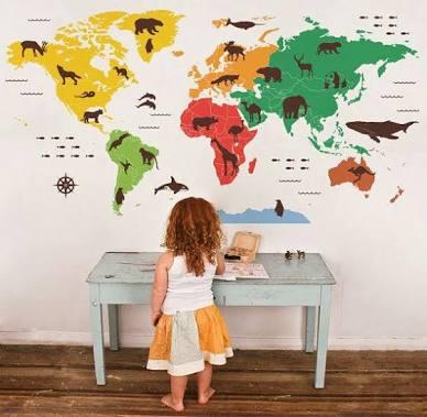 Imagem de uma menina e sua parede de decalque de mapas com os animais de cada país