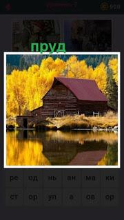 на берегу пруда расположен домик и деревья в желтом цвете