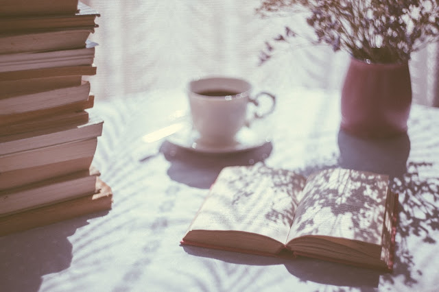 Image of an open book. There is a coffee cup in the background next to a vase. In the left of the image, there is a stack of books