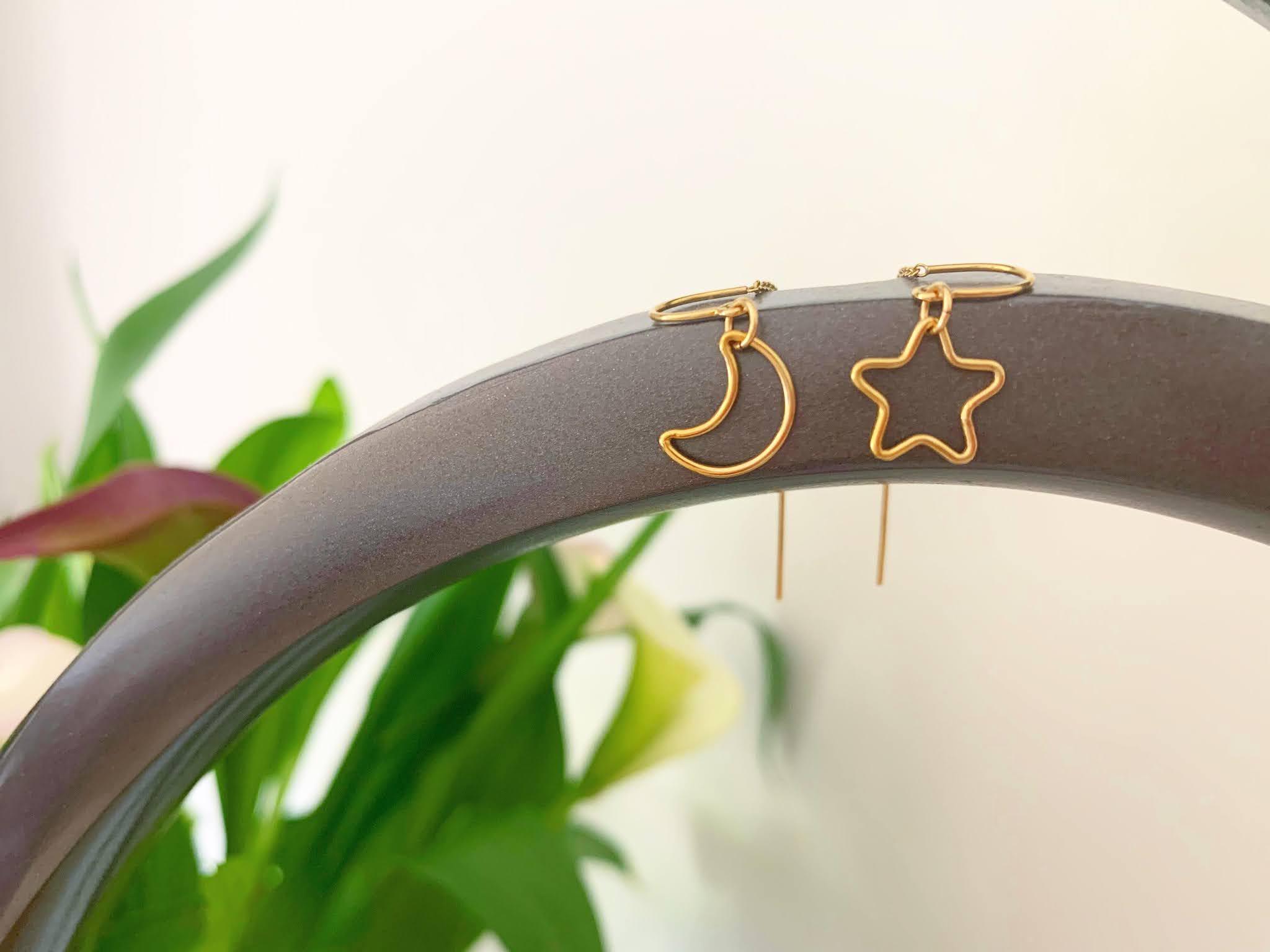 Binichohan Moon and Star Threader Earrings on a rail