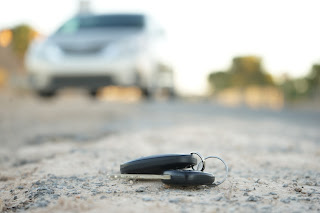 Keys are on ground with car in background