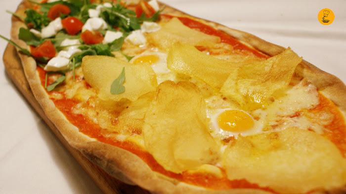 Pizza con patata fritas, huevos de codorniz y camembert en Trattoria Manzoni.