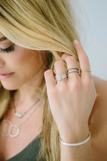 Model wearing multiple rings and silver bracelet from Silver and Salt Seattle