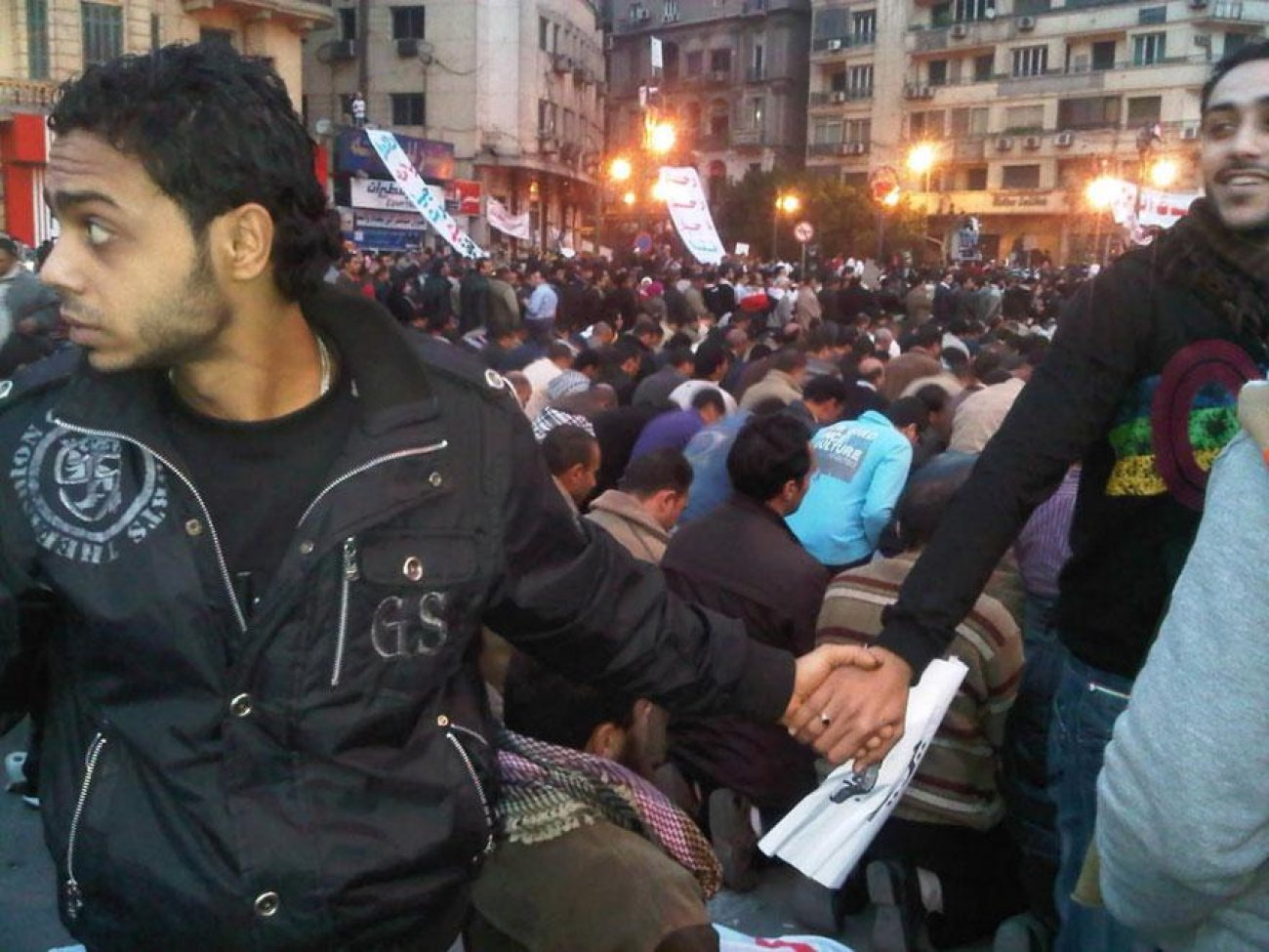 February 2011, Egypt Christians join hands to protect Muslims as they pray during Cairo protests.