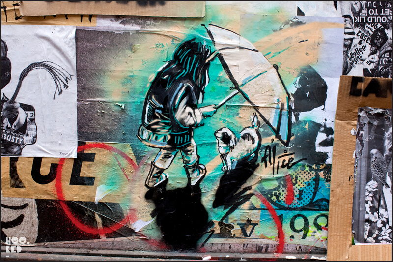 London street art by Alice Pasquini featuring a girls with an umbrella and small dog