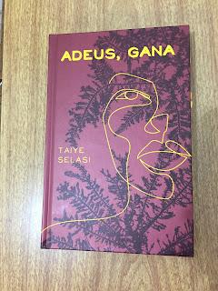 A imagem traz a foto do livro apresentado. Ele está sobre uma superfície de madeira e é marrom avermelhado. O título está escrito em amarelo no topo da capa. Sobre a ilustração de folha e galhos marrom escuros linhas amarelas formam a imagem de uma mulher.