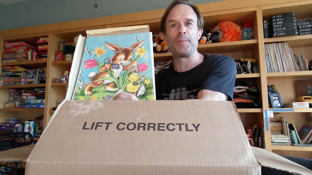 picture of guy behind a box holding vintage puzzle by a bookshelf