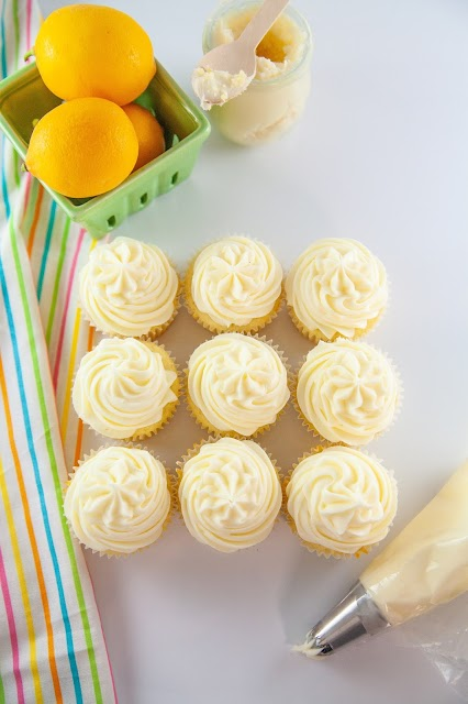 nine frosted cupcakes with piping bag