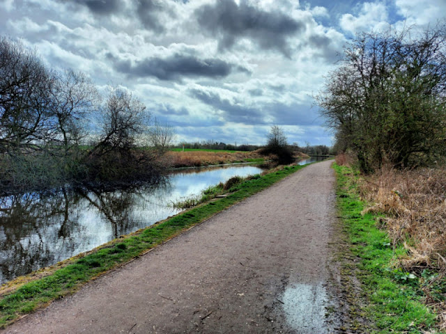 A footpath alongside a canal.  The trees are reflected in the water.