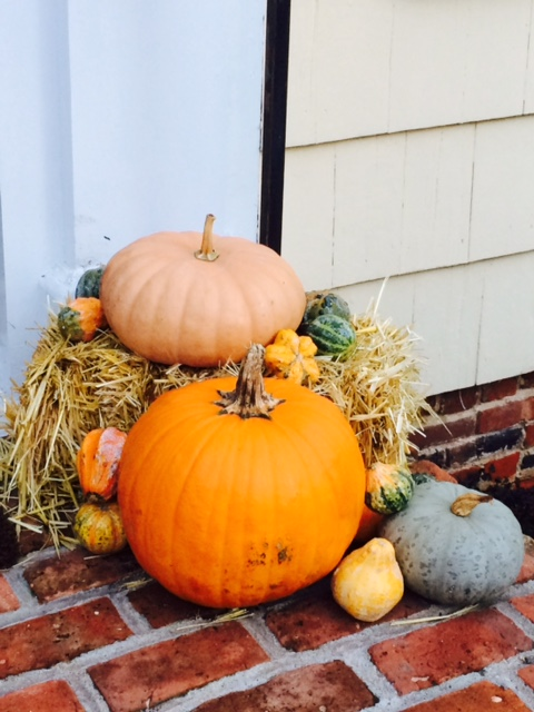 stack of pumpkins and gourds on brick porch