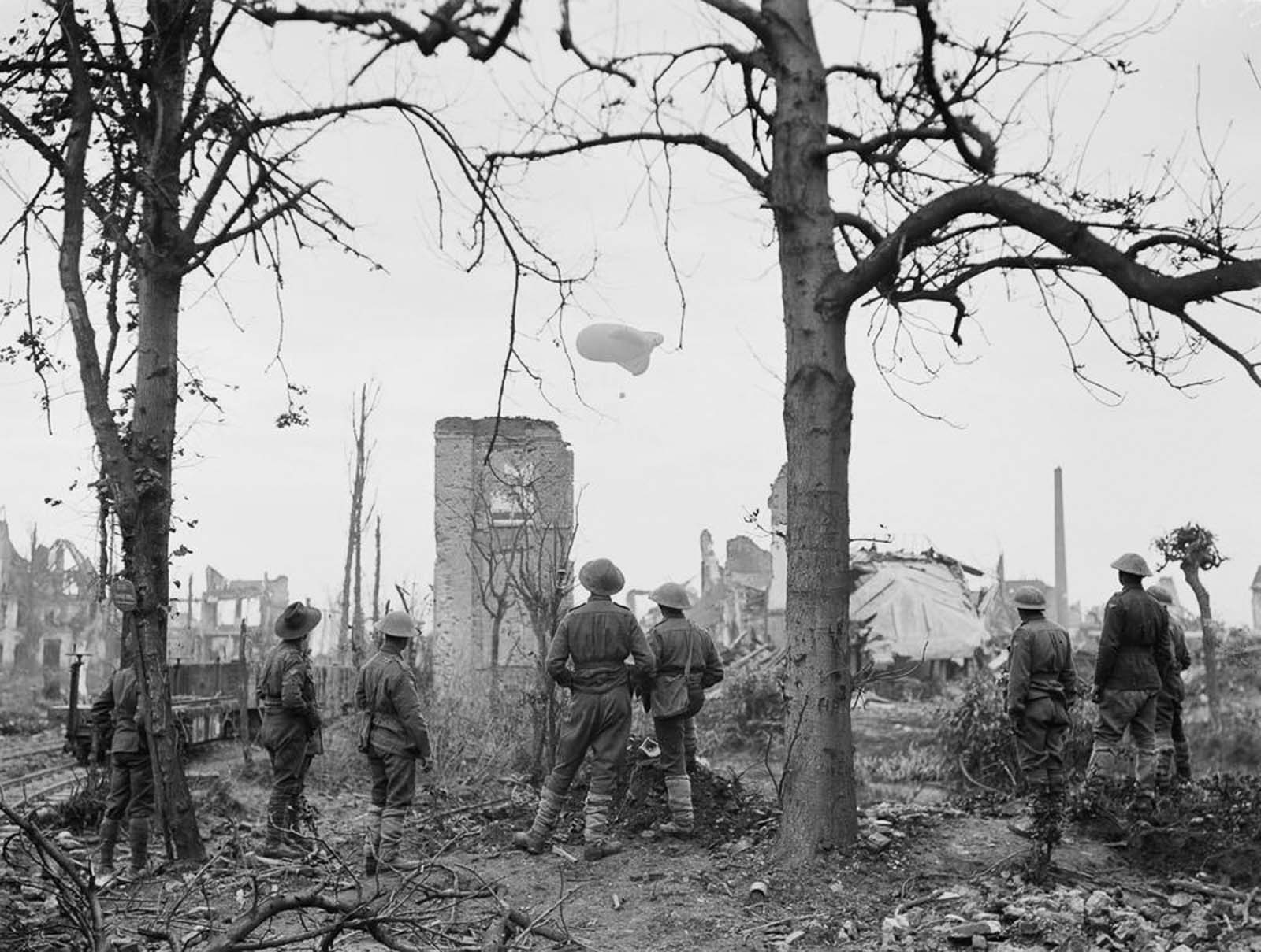 Australian soldiers watch an observation balloon ascend over Ypres, Belgium. 1917.