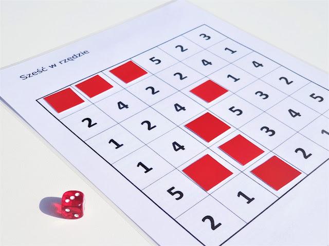na zdjęciu plansza sześć na sześć pól, na każdym polu liczby od jeden do pięć, częśc pól zakryta jest czerwonymi znacznikami a obok planszy leży czerwona kostka w wyrzuconą liczbą oczek-trzy