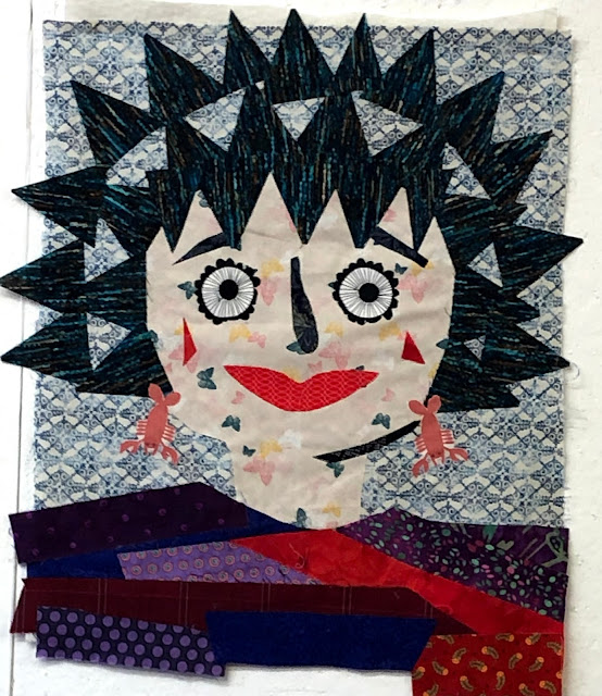 The pieces are glued to a background fabric to create a friendly female face.