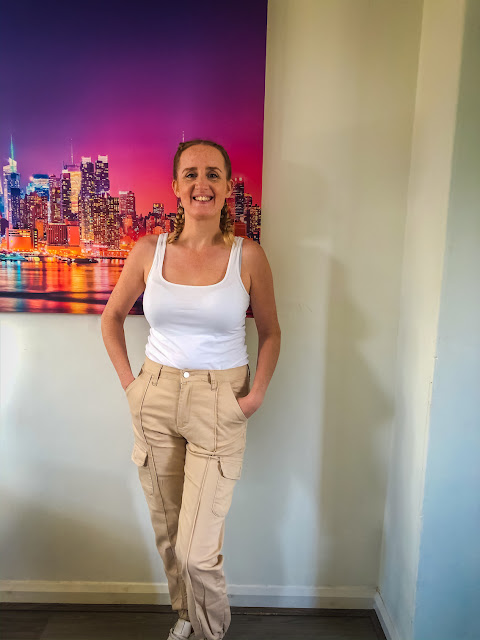 Comfy casual with Femme Luxe / standing in front of a large canvas with cream cargo trousers and white vest
