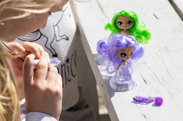 A tween holding out a plastic amulet they are wearing around their neck towards a Crystalina doll