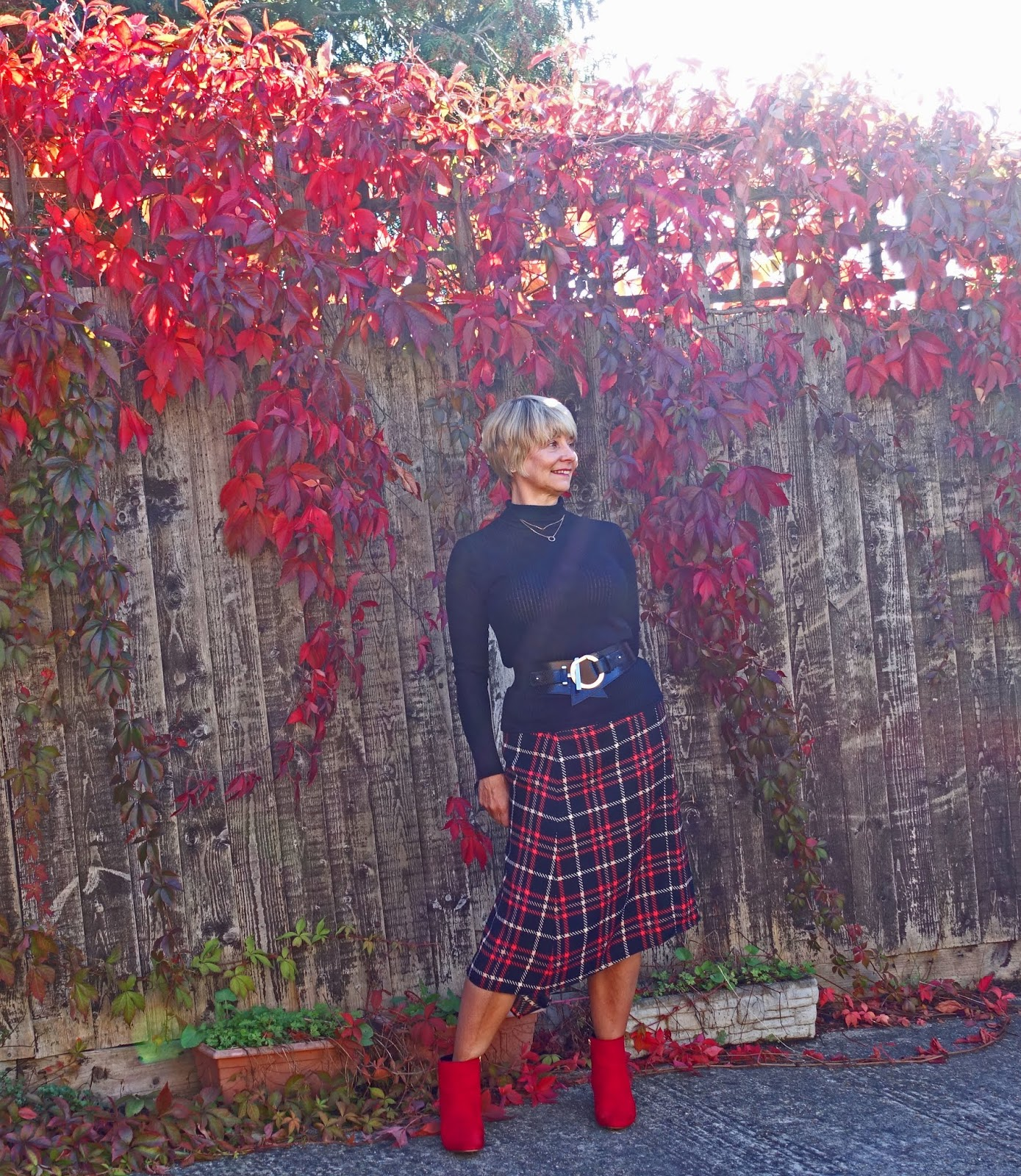 Against a Virginia creeper background, over 45s blogger Gail Hanlon in red check asymmetric skirt, black polo neck, red and black boots and jewellery from Happiness Boutique