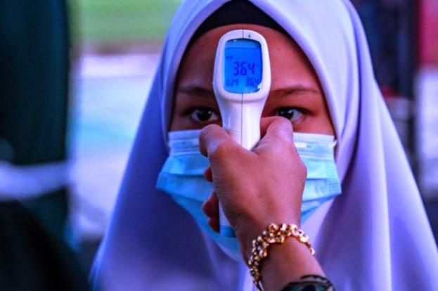 Ilustrasi pengecekan suhu tubuh Foto: AFP/MOHD RASFAN