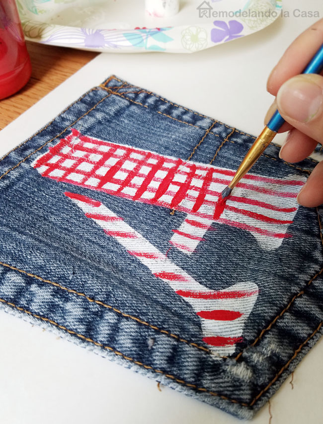 jean pocket with painted A adding red stripes with paint brush