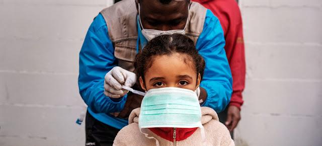 Una trabajadora de salud pone una mascarilla médica a una niña antes de su consulta en Roma, Italia.UNICEF/Alessio Romenzi