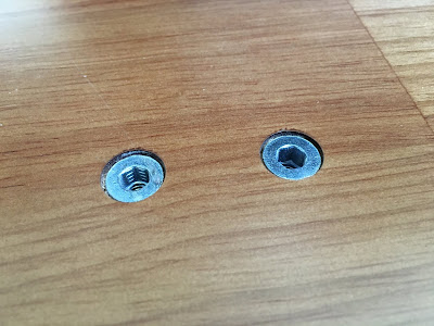 Wood nut inserts on the underside of the desk