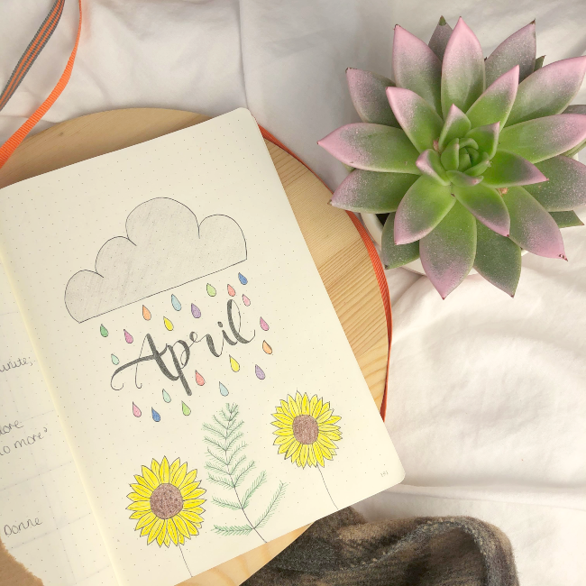 Open journal with the word april written between a cloud and some sunflowers. Next to a small cactus