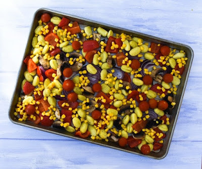 Easy Roasted Vegetable Gnocchi Bake - Step 2 Add sweetcorn and cherry tomatoes to the part baked veg