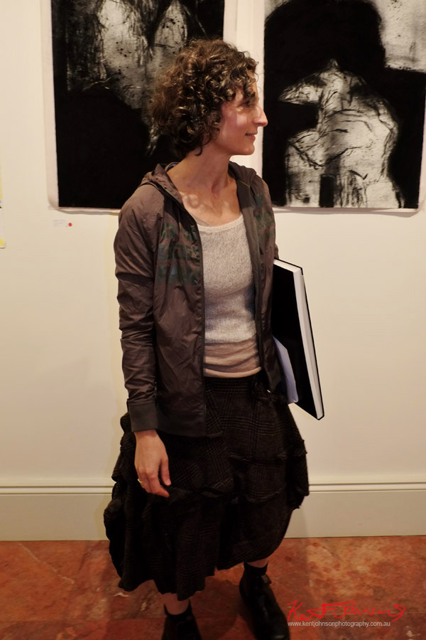 Artist portrait Marta Ferracin with two charcoal drawings, RM Williams boots, ruffled check skirt, grey singlet top and parka - Art Opening - Street Fashion Sydney