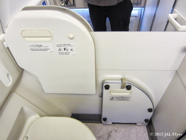 JAL F lavatory - You can pull down the board to cover the floor when you change your clothes