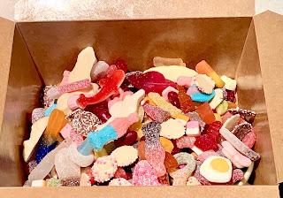 A large light brown rectangular box filled with a variety of different shaped and coloured sweets on a bright background