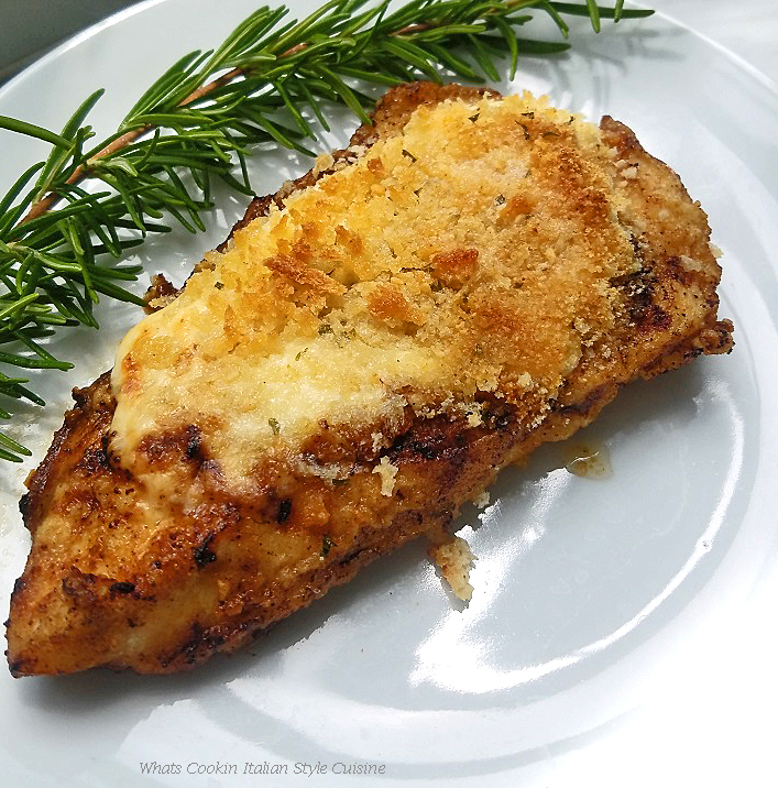 This is a piece of chicken topped with melted cheeses and a sprig of rosemary on a white plate