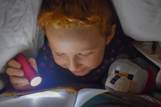 anak baca buku dalam gelap