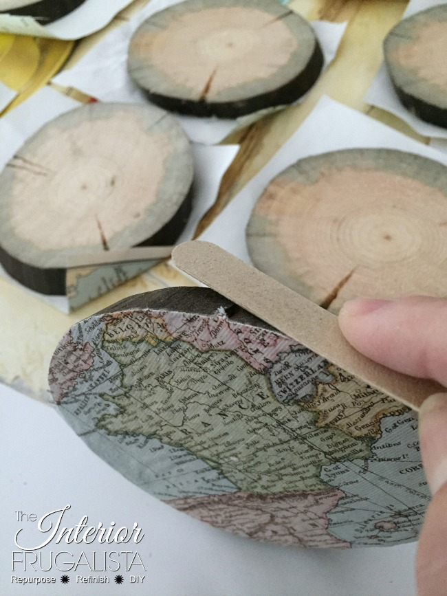 Emery board to file edges of decoupaged wood slice map ornaments