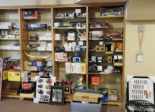 A collection of toys for sale in a basement shelving unit.