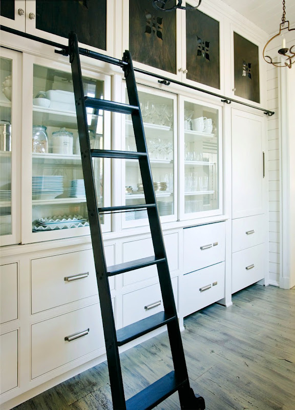 Organized white pantry with a black ladder on wheels to make reaching high cabinets easier