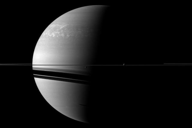 Hai mặt trăng nhỏ Rhea và Dione xuất hiện phía trước Sao Thổ trong hình ảnh chụp từ tàu Cassini vào ngày 11 tháng 3 năm 2011. Rhea nằm ở bên phải, còn Dione nằm ở bên trái, chúng là vệ tinh lớn thứ hai và thứ tư của Sao Thổ. Vệ tinh Tethys cũng xuất hiện trong hình ở phần dưới đáy nhưng rất khó thấy được. Hình ảnh: NASA/JPL.