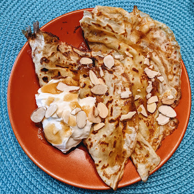 Overhead shot of two crepes with barbados cream, a brown sugar drizzle, and almonds.